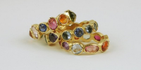 9 stone rings in 18k gold with sapphires and tourmalines.